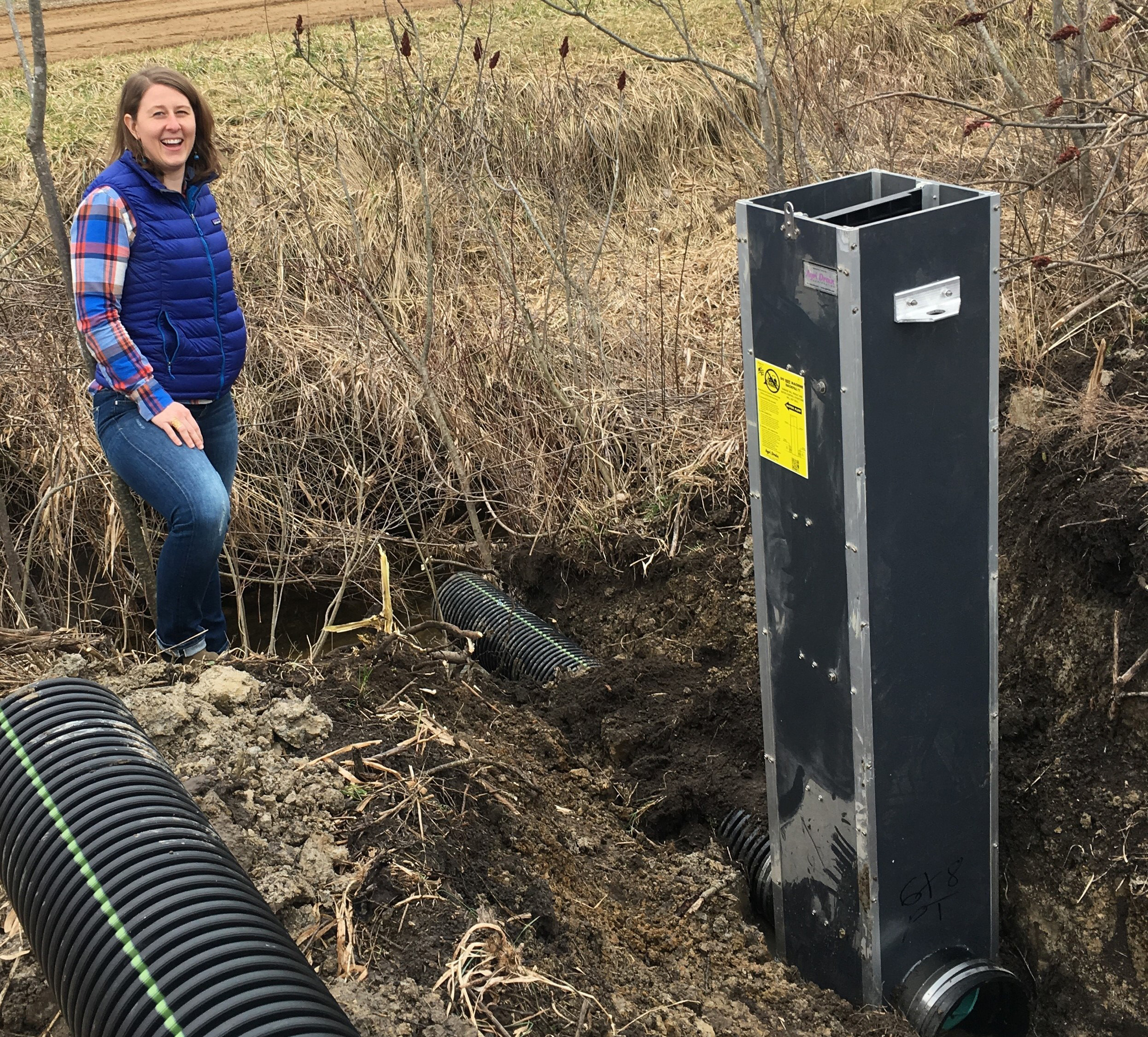 Colleen Forestieri of Van Buren CD oversees installation of a water control structure that helps reduce runoff from farm fields and hold water in the field during drought periods.